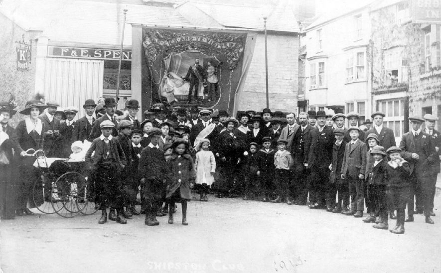 Members of a Shipston on Stour benefit club parading in street with banner which depicts sick man with wife and child being visited by club official. Inscription