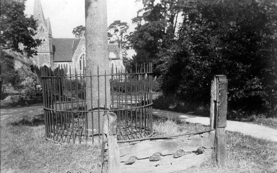 The stocks at Lower Shuckburgh, with St John the Baptist church in the background. These stocks have now completely disappeared but their are plans to re-erect new ones in their place as part of the millennium project.  1920s |  IMAGE LOCATION: (Warwickshire County Record Office)
