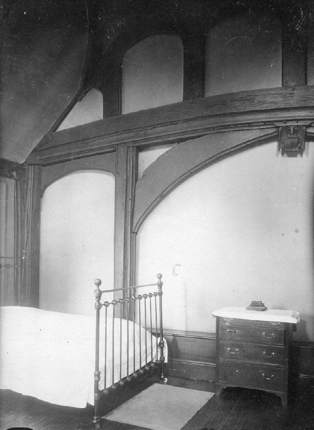 Manor House, Upper Great Hall Long Itchington, showing a bed and chest of drawers.  1920s |  IMAGE LOCATION: (Warwickshire County Record Office)