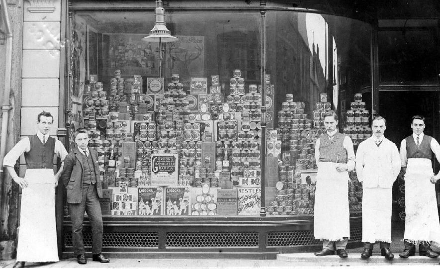 Picture of a grocer's shop front, the staff standing outside. No indication of whereabouts, but post marked Stratford 0n Avon.  1900s |  IMAGE LOCATION: (Warwickshire County Record Office)