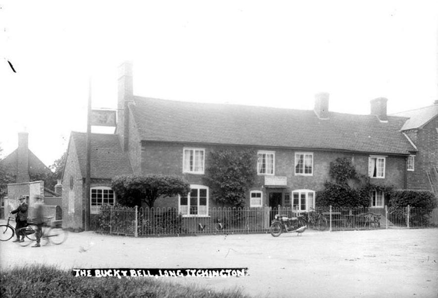 The Buck and Bell showing two men with bicycles and a parked motor-cycle, Long Itchington.  1920s |  IMAGE LOCATION: (Warwickshire County Record Office)