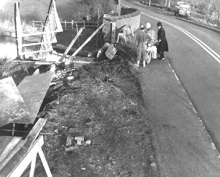 Cuttle Bridge, Long Itchington showing damage to the footbridge caused by a lorry. There are two workmen and a policeman leaning on his Velocette motorbike.  There is a BBC van in the background.  27th Jan 1964