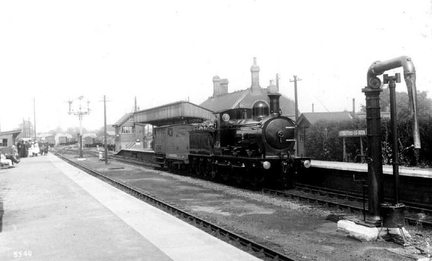 A locomotive passing through Stratford upon Avon station. 1900s[The correct location of this photograph is the Seven Sisters Meadow Road roundabout by Greenways car park and Old Town Mews. This was the site of the Midland Junction Railway Station. The road is in fact built on the old trackbed.] |  IMAGE LOCATION: (Warwickshire County Record Office)
