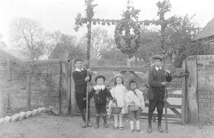 Long Itchington outside a farm gate showing children dressed for May Day and holding a garland.  1910s |  IMAGE LOCATION: (Warwickshire County Record Office)