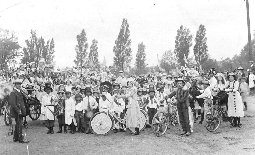A large group of children and adults dressed for a carnival, possibly May Day with decorated bicycles, Long Itchington.  1911 |  IMAGE LOCATION: (Warwickshire County Record Office)
