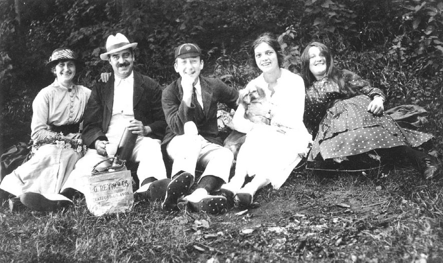Family group of two adults and three teenage children enjoying a picnic. Note the carrier bag from G. Reynolds, grocers, Stratford upon Avon.  1910s |  IMAGE LOCATION: (Warwickshire County Record Office)