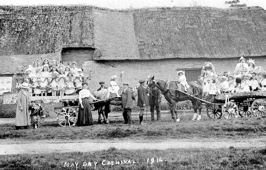 Children on two horsedrawn floats in front of a thatched barn, Long Itchington.  1914 |  IMAGE LOCATION: (Warwickshire County Record Office)