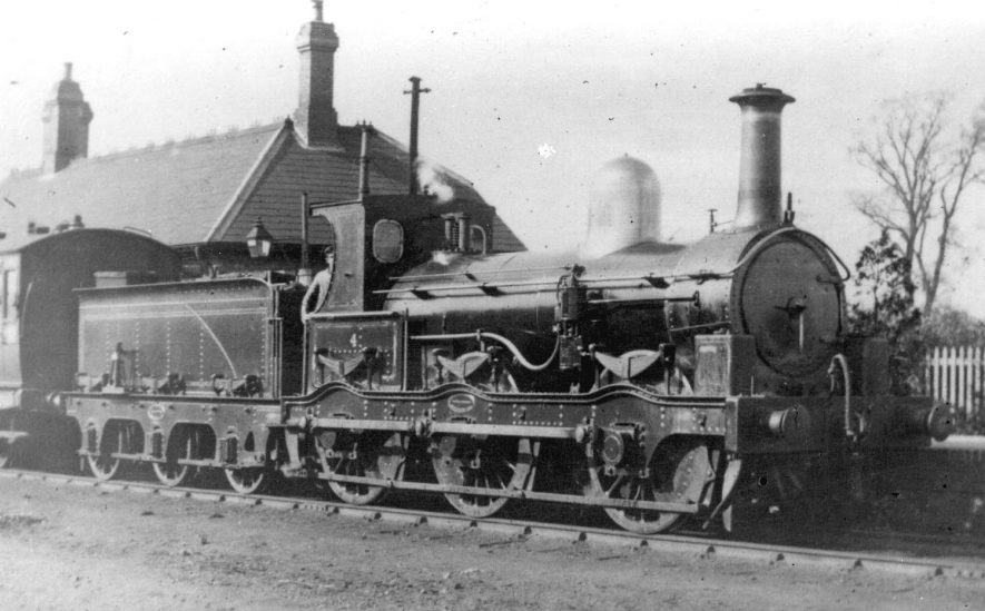 Steam engine E & W J. R. 0-6-0 No.4, built by Beyer Peacock (Manchester) in 1885 and withdrawn from service and scrapped in 1930. Engine pictured standing in Stratford Old Town station in the early 1890s.[The correct location of this photograph is the A4390 Seven Sisters roundabout by Greenways car park and Old Town Mews. This was the site of the Midland Junction Railway Station. The road is in fact built on the old trackbed.] |  IMAGE LOCATION: (Warwickshire County Record Office)