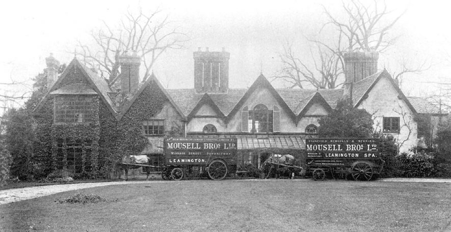 Two removal horse and carts belonging to Mousell Bros. Ltd. Leamington Spa, outside the rear of The Alveston Manor Hotel, Stratford upon Avon.  1910s |  IMAGE LOCATION: (Warwickshire County Record Office)