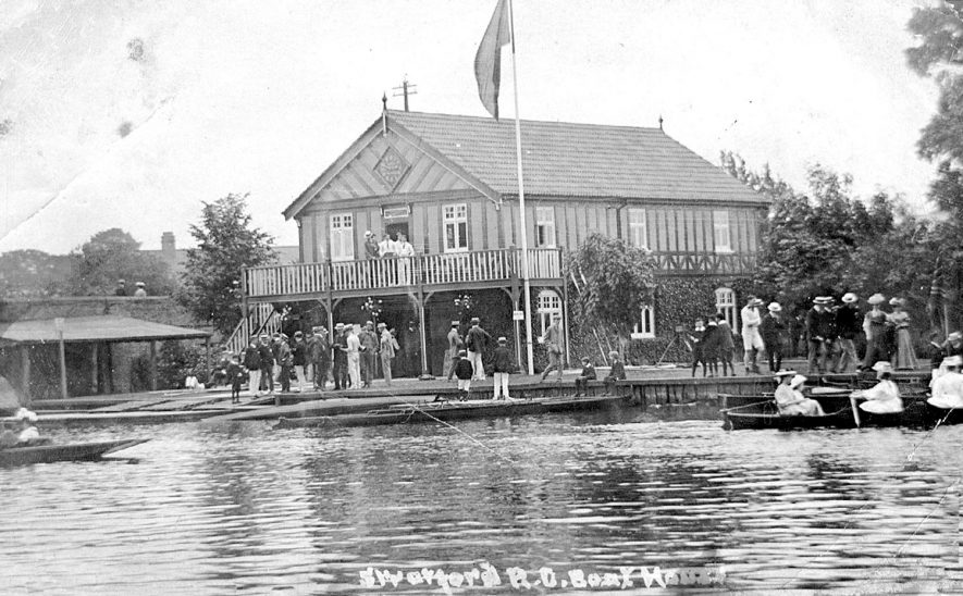 The boat house on the River Avon at Stratford, with groups of people on the bank and in boats.  1910s