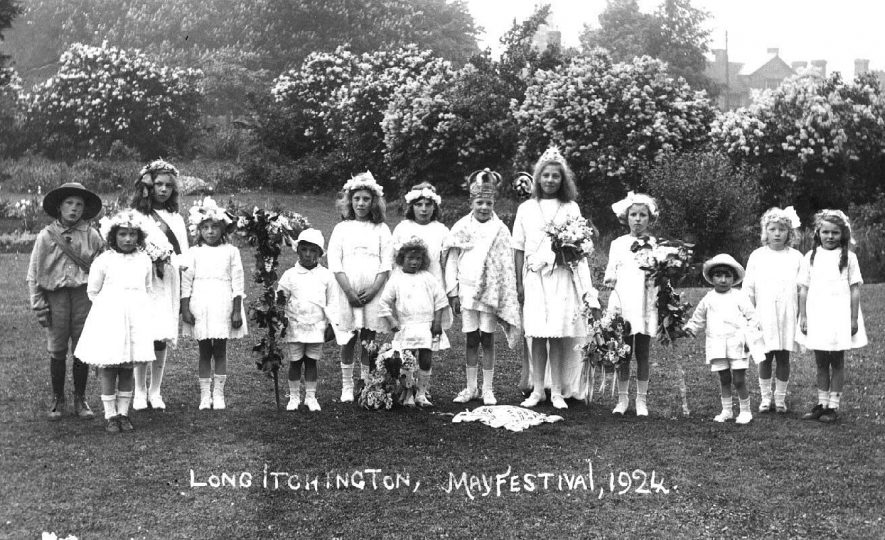 May Day Long Itchington, in showing children in fancy dress and with garlands of flowers. The girl on the extreme right is Rhona Roberts and next to her is Annie White.  1924 |  IMAGE LOCATION: (Warwickshire County Record Office) PEOPLE IN PHOTO: White, Annie, Roberts, Rhona