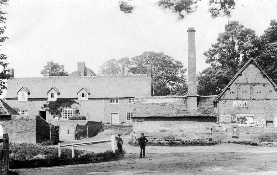 Cottages and barn with chimney on corner of Wappenbury and Coventry Roads, Princethorpe.  1900s |  IMAGE LOCATION: (Warwickshire County Record Office)