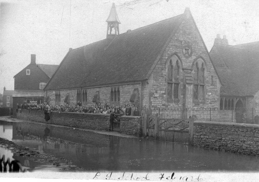 Long Itchington School after 'the floods' showing school pupils and teachers standing outside the school with the flood water in the foreground.  1926 |  IMAGE LOCATION: (Warwickshire County Record Office)