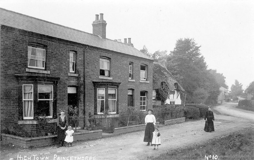 High Town, Princethorpe.  Terraced housing and thatched cottage with women and children in the street.  1900s |  IMAGE LOCATION: (Warwickshire County Record Office)