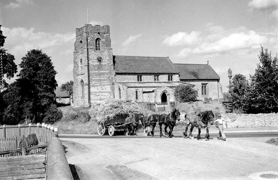 A horse and cart loaded with hay, drawn by a boy leading 4 horses. Ufton Church in the background.  1951 |  IMAGE LOCATION: (Warwickshire County Record Office)
