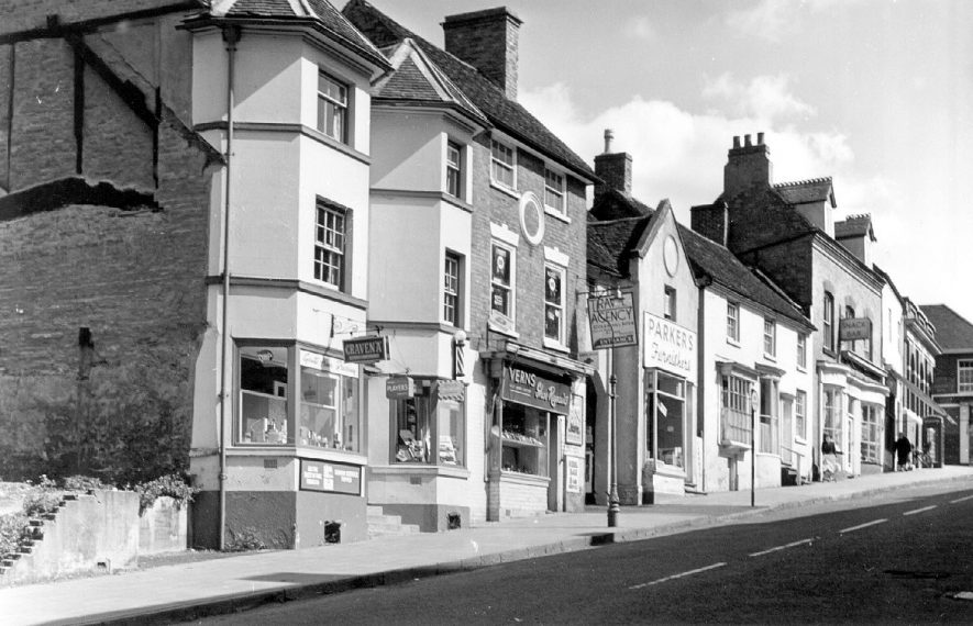 Shops going up the hill - Barbers, Vern's shoe repairs with travel agents above, Parker's furnishers, Pattison's tea bar, Midland Bank, East side of High Street, Coleshill.  1964 |  IMAGE LOCATION: (Coleshill Library)