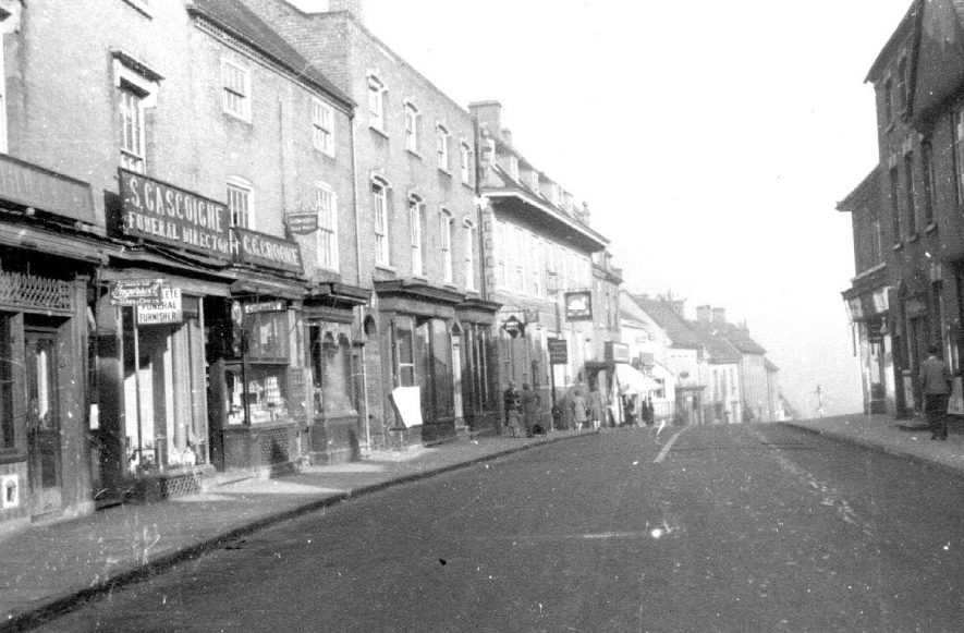 Hull's butchers, Gascoignes funeral furnishers, chemist, Miller's haberdashery and The Swan Inn, High Street, Coleshill.  1944 |  IMAGE LOCATION: (Coleshill Library)