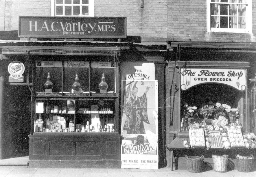 H.A. Varley, chemist, Gwen Breeden, flowers and greengrocery, High Street, Coleshill.  Advertising - The Mikado, Coleshill Operatic Society.  1950s    IMAGE LOCATION: (Coleshill Library)