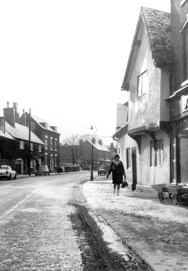 High Street, Coleshill after snow. Mr Miller's cottage, the oldest in Coleshill. Also in picture Coleshill Cottage and Fern Cottage on the left.  1960s |  IMAGE LOCATION: (Coleshill Library)