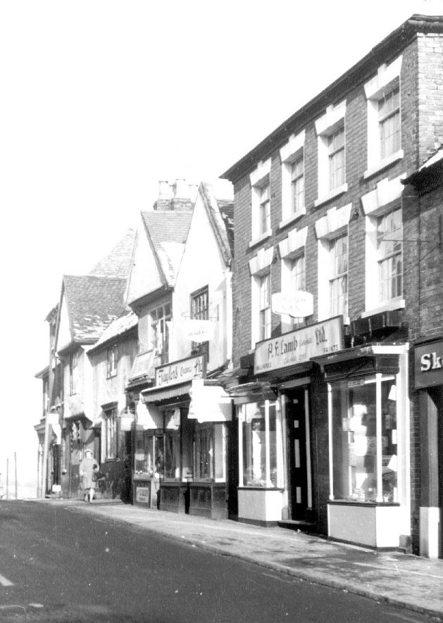 High Street, Coleshill, above Church Hill. 'Sketchley's' laundry on extreme right, P.F. Lamb - butcher and Taylors shops. Advertising signs for Walls ice cream and Calor Gas.  1970 [Sign over the shop is clearly written 'Paint & Wallpaper', retailer P. F. Lamb] |  IMAGE LOCATION: (Coleshill Library)