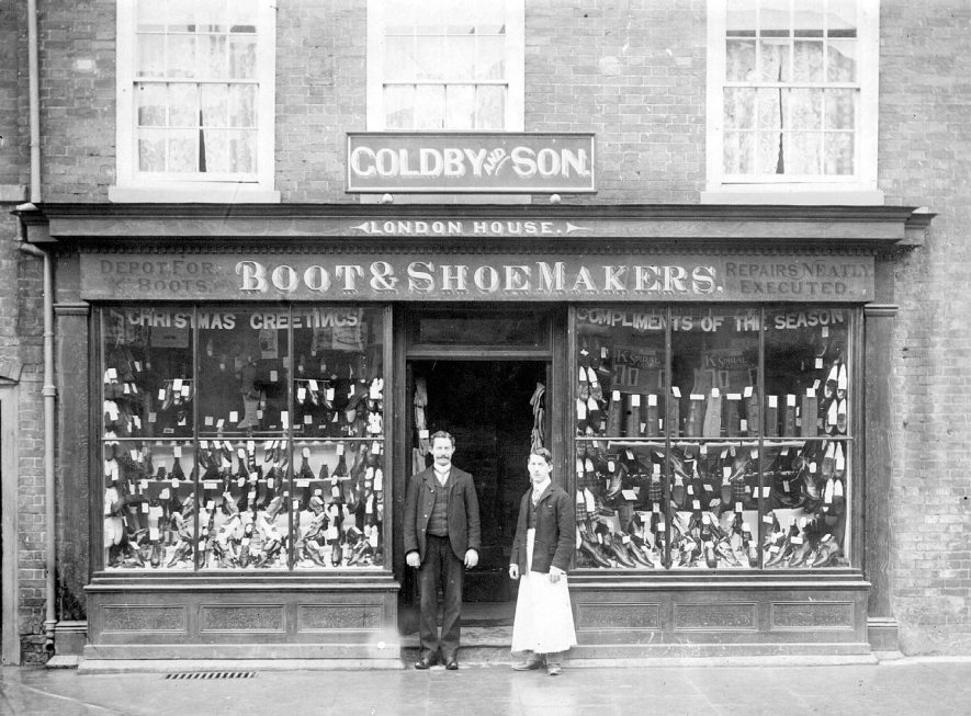 Goldby and Son, Boot and Shoemakers, London House, High Street, Coleshill.  Tom Goldby with his son Stanley who later used the backroom as an office for registering births and deaths.  1900s |  IMAGE LOCATION: (Coleshill Library) PEOPLE IN PHOTO: Goldby, Tom, Goldby, Stanley, Goldby as a surname