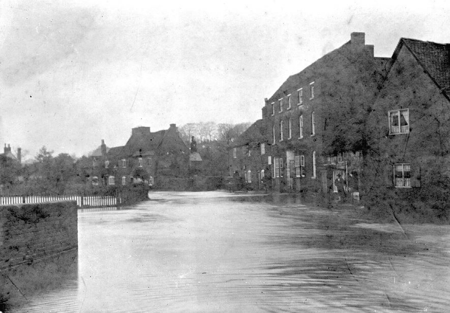 Flooding at the bottom of Coleshill Hill, Lower High Street, Coleshill. The three storey building was originally the Queen's Head public house.  1900 |  IMAGE LOCATION: (Coleshill Library)