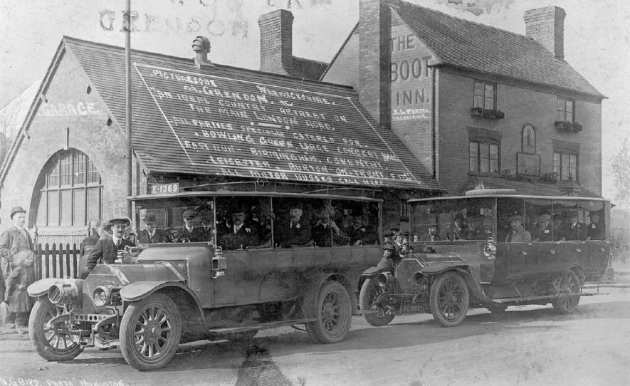 Two motor buses standing outside The Boot Inn, Grendon, ready for departure for a tour around Warwickshire.  1900s |  IMAGE LOCATION: (Atherstone Library)