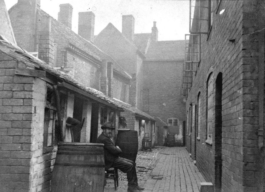 16 -18 Cleobury's Buildings, Atherstone. Mr. King sitting beside a large water butt.  1900s |  IMAGE LOCATION: (Warwickshire County Record Office) PEOPLE IN PHOTO: Kind, Mr, Kind as a surname