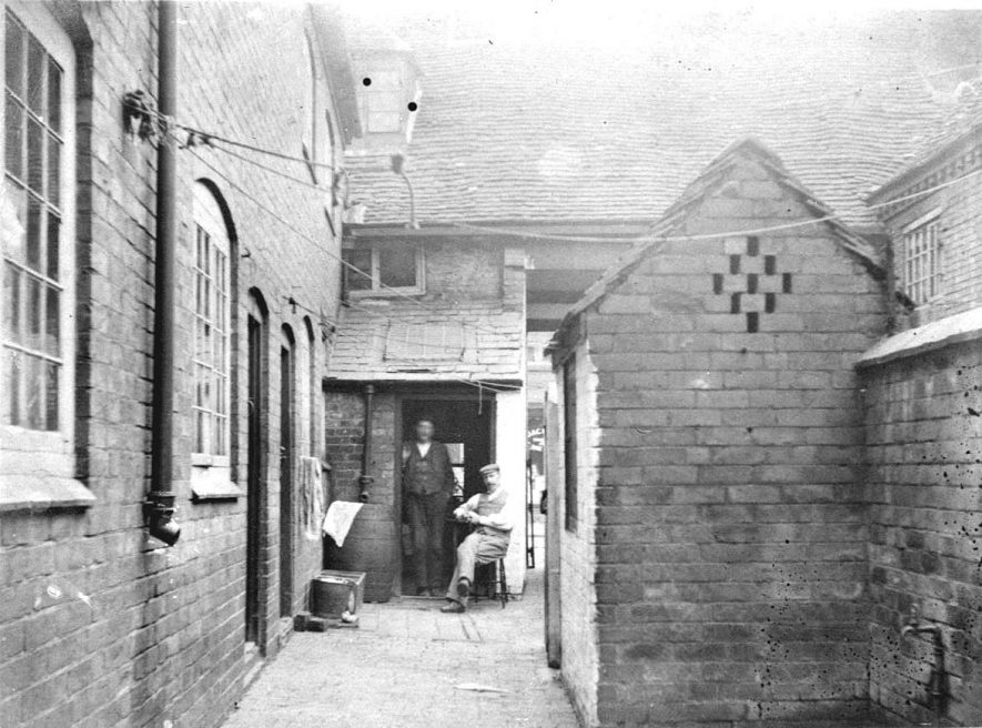 48-50 Brown Bear Yard or Crown Yard, looking towards the street, Atherstone. A group of men in the doorway.  1900s |  IMAGE LOCATION: (Warwickshire County Record Office)