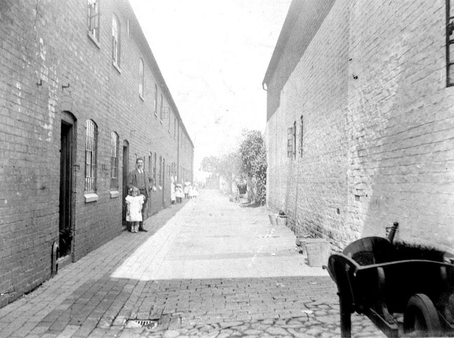 14-16 Garden Row, Atherstone, which have now been demolished. Inhabitants can be seen in doorways and a wooden wheelbarrow in the foreground.  1900s |  IMAGE LOCATION: (Warwickshire County Record Office)