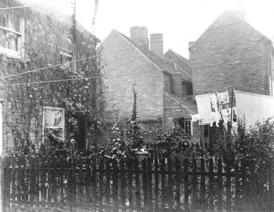 49-51 Swan & Two Nicks Yard, Atherstone.   Brick cottage with garden, ends of terrace housing, washing on line.  1900s