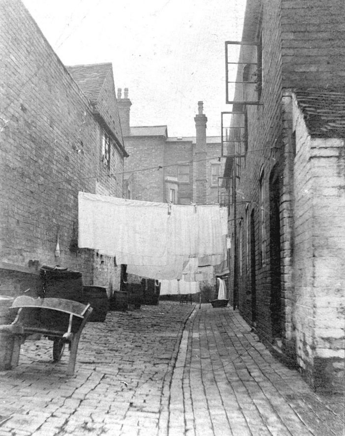 White Lion Yard off Station Street, Atherstone.  Washing on line and wooden wheelbarrow.  1900s    IMAGE LOCATION: (Warwickshire County Record Office)