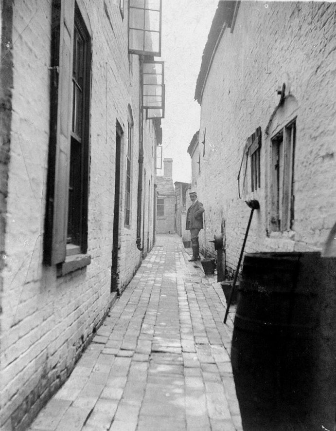 19 & 21 Bosse's Yard, Atherstone, with Tom Johnson standing.  1900s |  IMAGE LOCATION: (Warwickshire County Record Office) PEOPLE IN PHOTO: Johnson, Tom, Johnson as a surname