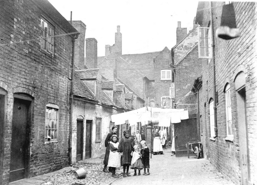 23-25 Avin's Yard, Atherstone, looking towards Long Street.  Children, women and washing lines.  1900s |  IMAGE LOCATION: (Warwickshire County Record Office)