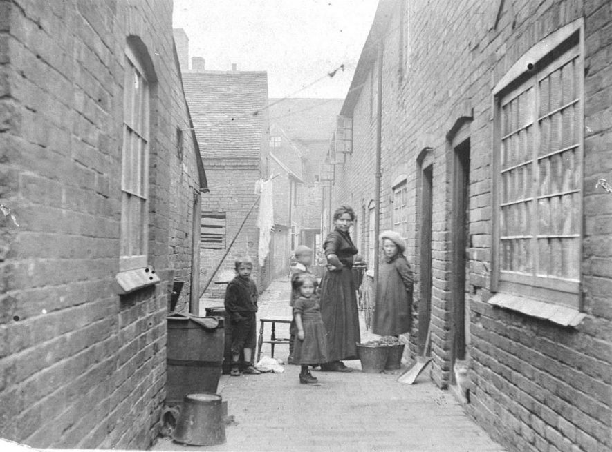 81-83 Hand & Bottle Yard towards Long Street.  No 81 was formerly the Hand & Bottle public house.  Housewife and group of children standing.  1900s |  IMAGE LOCATION: (Warwickshire County Record Office)