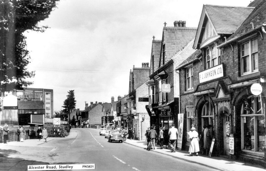 Shops, cars and people in Alcester Road, Studley.  1960s |  IMAGE LOCATION: (Warwickshire County Record Office)