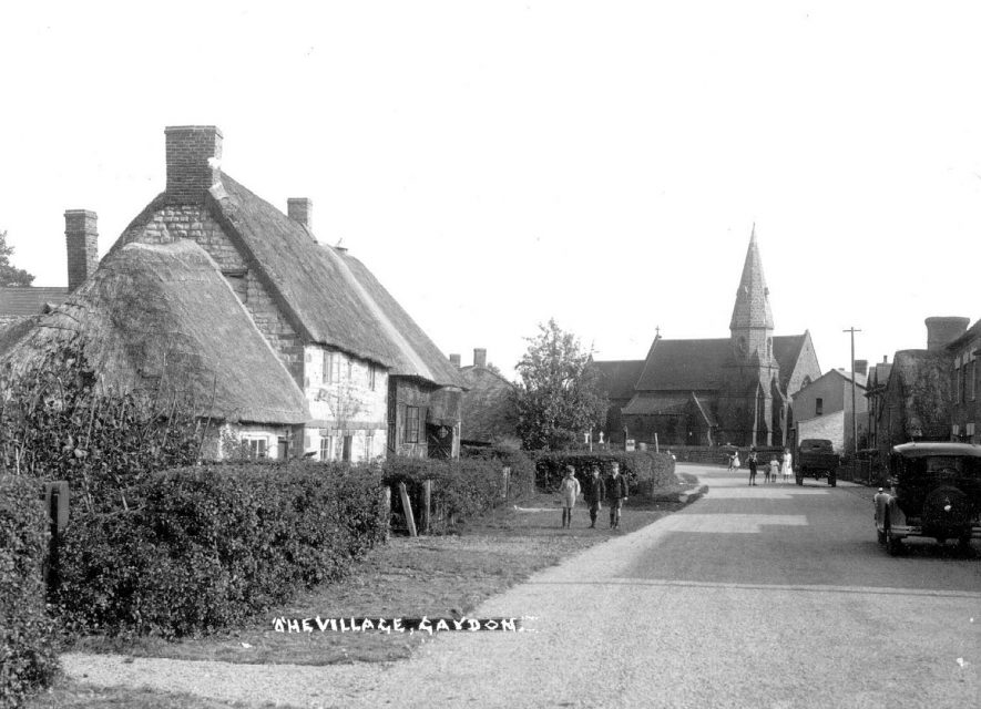 Gaydon looking towards the church with thatched cottages and the County Library on the left. There are children in the street and a motorcar on the left  (number plate OG 3492).  1950s |  IMAGE LOCATION: (Warwickshire County Record Office)