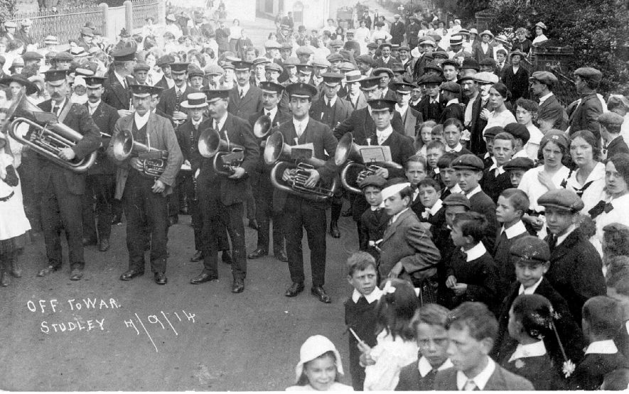 Brass band and large group of followers at the outbreak of the first World War. Studley. September 7th 1914.[The child in the Eton collar in the centre of the photograph was John Thompson who later became a local brewer] |  IMAGE LOCATION: (Warwickshire County Record Office)