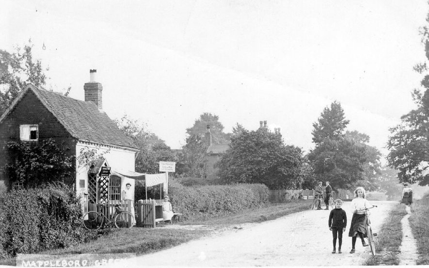 Hannah Wild's grocery store with children and adults and their bicycles in the road at Mappleborough Green.  1910s |  IMAGE LOCATION: (Warwickshire County Record Office)