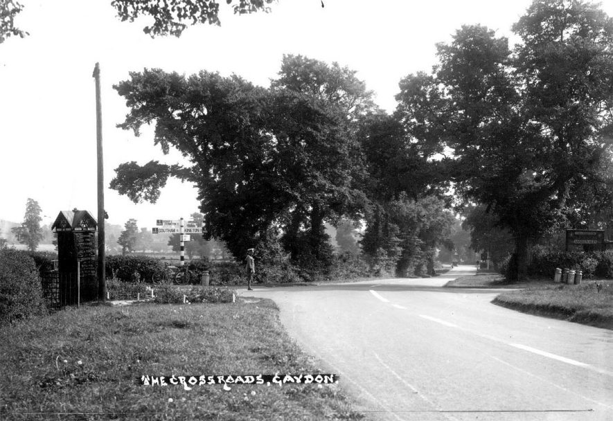 The crossroads near the Malt Shovel Inn. An AA patrolman is standing at the crossroads and an AA telephone box is to the left.  1950s |  IMAGE LOCATION: (Warwickshire County Record Office)