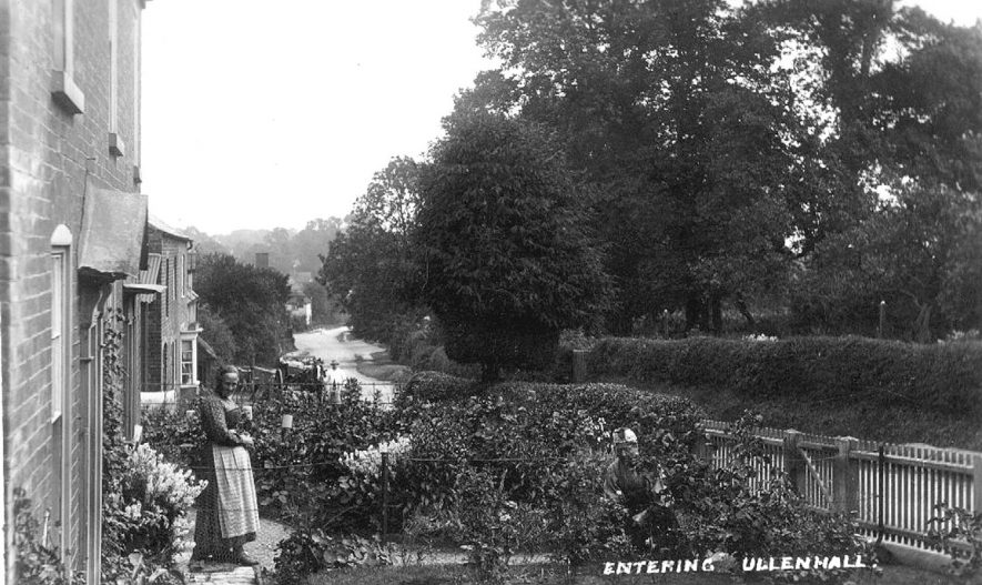 Entering Ullenhall, with man and woman in the garden of their cottage.  1910s |  IMAGE LOCATION: (Warwickshire County Record Office)