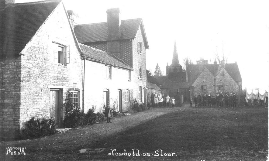 Cottages, school and school children, spire of parish church, Newbold on Stour.  1900s |  IMAGE LOCATION: (Warwickshire County Record Office)