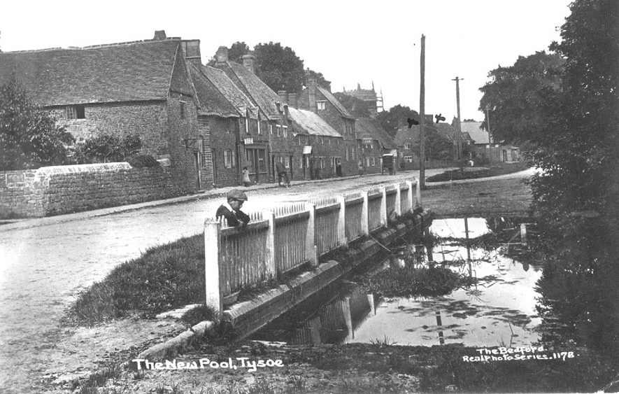 Young lad contemplating the New Pool, where the stream is crossed by the road.  1910s |  IMAGE LOCATION: (Warwickshire County Record Office)