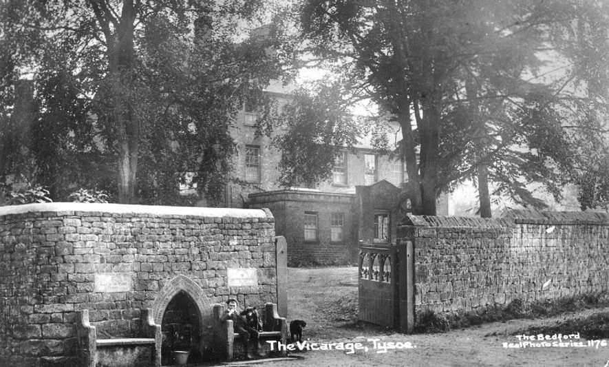 Young lad and his dog waiting for the pail to fill with water from the spring, which is situated in the wall outside the vicarage.  1910s |  IMAGE LOCATION: (Warwickshire County Record Office)
