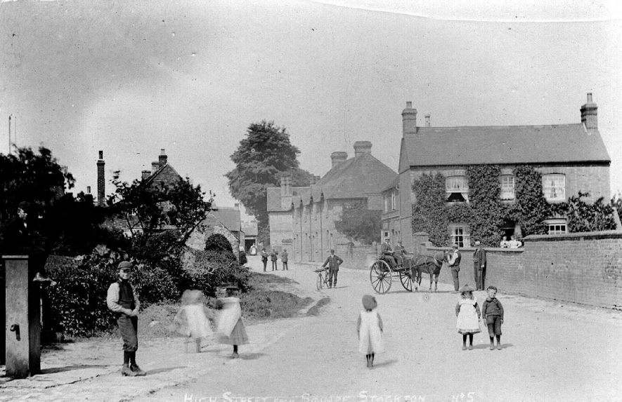 View along Stockton High Street from The Square showing children by the village pump and a horse and trap plus a postman and his bicycle.  1920s    IMAGE LOCATION: (Warwickshire County Record Office)