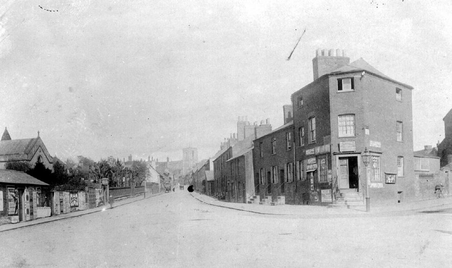 Friar's Street seen from corner of Compton Street, Warwick.  Terraced housing and a shop.  Part of St Paul's Church on left.  1900s |  IMAGE LOCATION: (Warwickshire County Record Office)