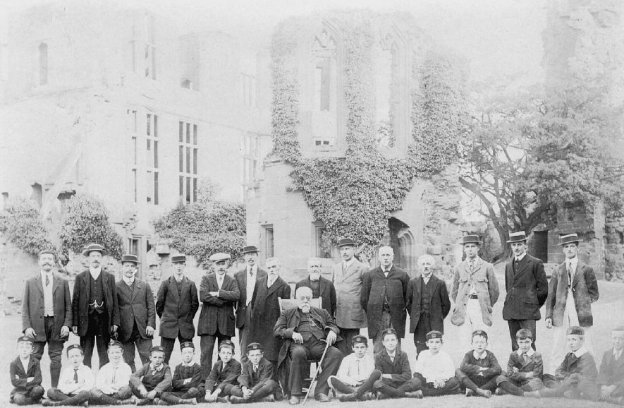 Dr. Dickens, Vicar of All Saint's church, Warwick, with the choir at Kenilworth Castle.  1910s |  IMAGE LOCATION: (Warwickshire County Record Office) PEOPLE IN PHOTO: Dickins, Revd Thomas Bourne