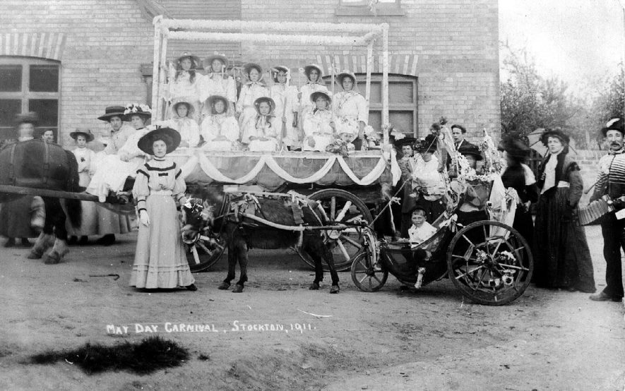 May Day 1911 showing a horse drawn decorated float on which are ten girls and in front a pony drawn three wheeled carriage in which sits a child. All the people are dressed up in their finery and there is one man in fancy dress holding an accordion, Stockton.  1911 |  IMAGE LOCATION: (Warwickshire County Record Office)