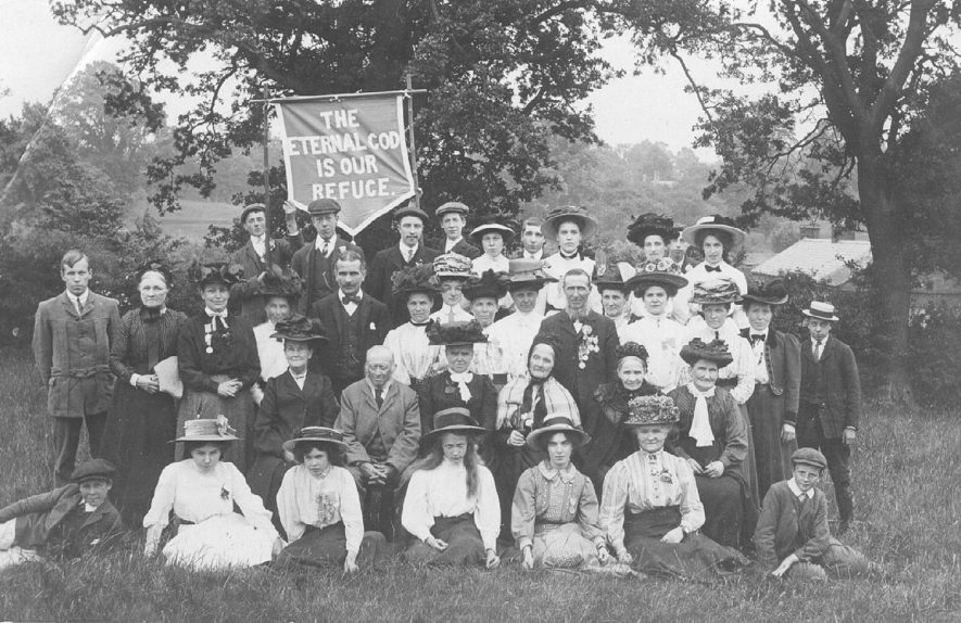Group of men, women and young people holding a banner stating