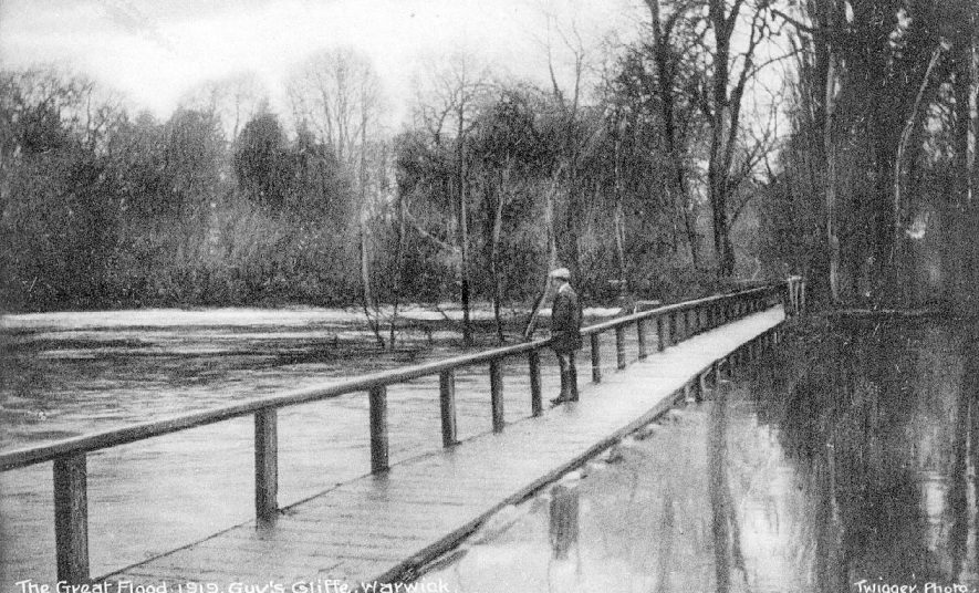 Man standing on wooden footbridge looking at the floods at Guy's Cliffe, Warwick.  1919 |  IMAGE LOCATION: (Warwickshire County Record Office)